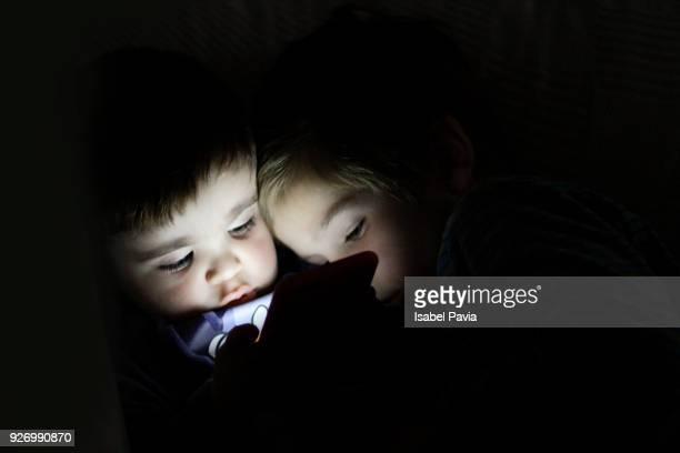 Siblings using digital tablet in the dark