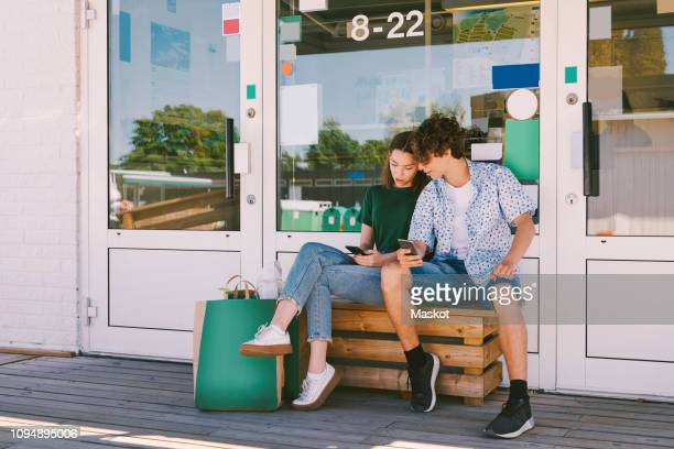 siblings using mobile phone while sitting on bench with bags outside information booth - chiuso per ferie foto e immagini stock