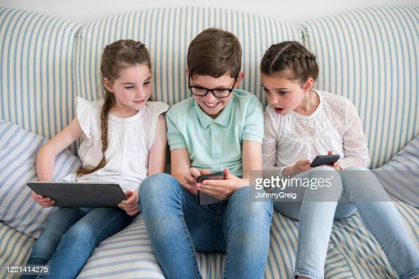 siblings using smartphone and digital tablet on sofa at home - three people stock pictures, royalty-free photos & images
