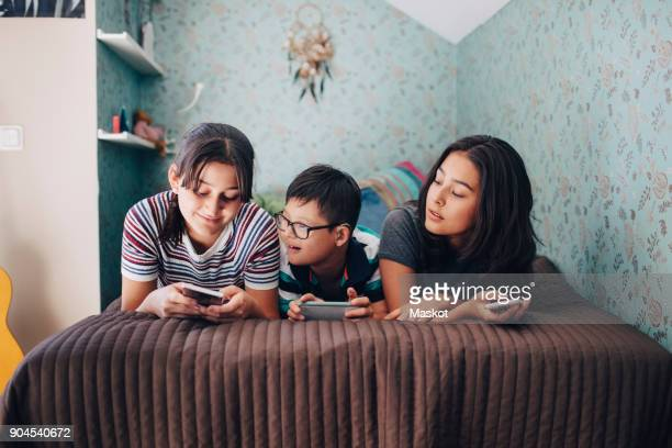siblings using wireless technologies while lying on bed by wall at home - disabilitycollection stock-fotos und bilder