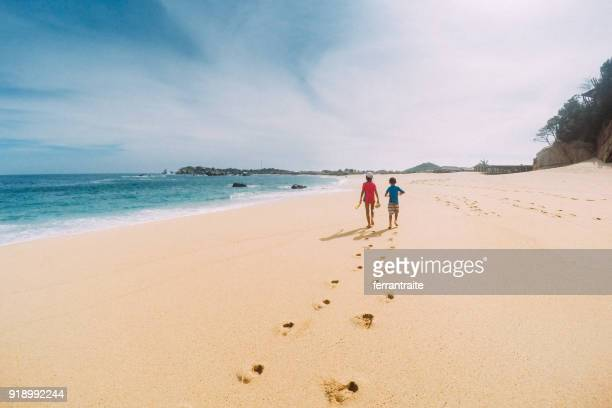 siblings walk a deserted oaxaca beach in mexico - oaxaca stock pictures, royalty-free photos & images