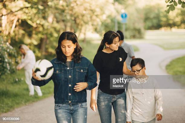 siblings walking on pathway with parents in background at park - lane sisters stock photos and pictures