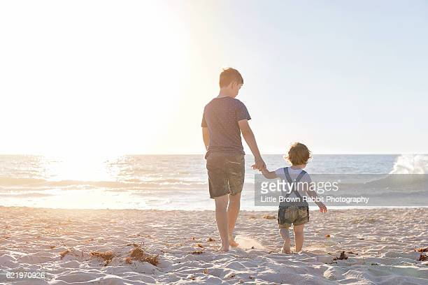 Siblings Walking on the Beach Shoreline at Sunset