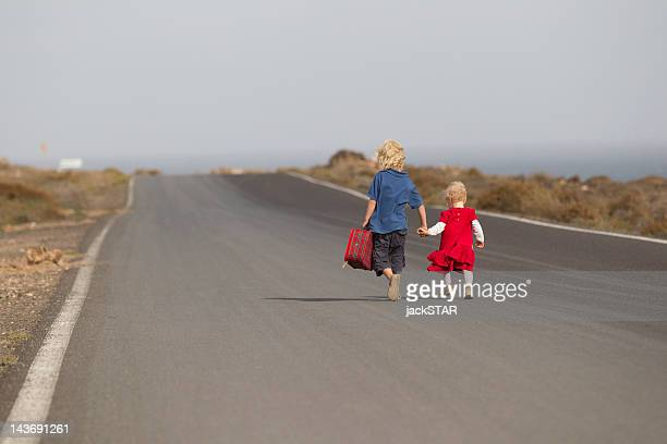 siblings walking together on rural road - runaway stock pictures, royalty-free photos & images