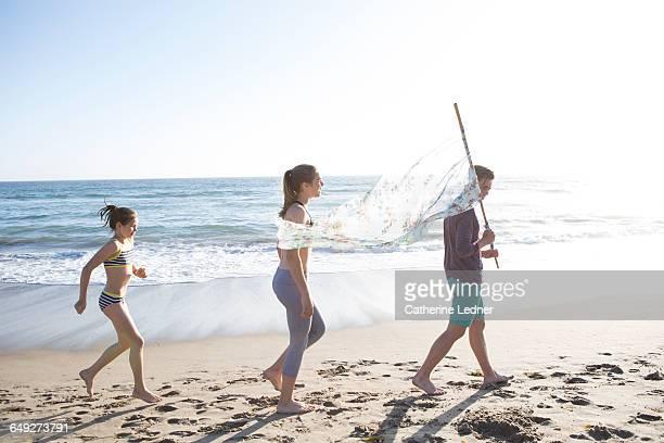 Siblings walking with flag on beach