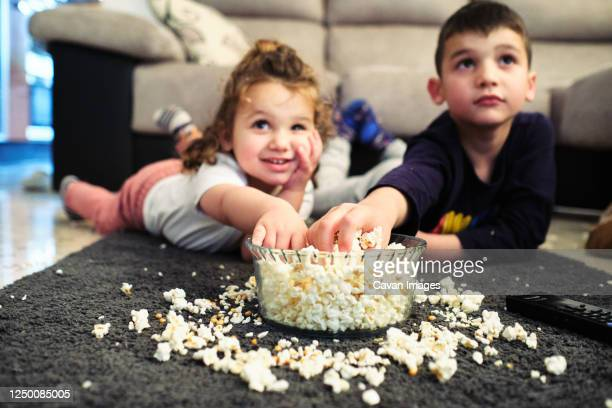 siblings watching a home movie while eating popcorn - film stock pictures, royalty-free photos & images