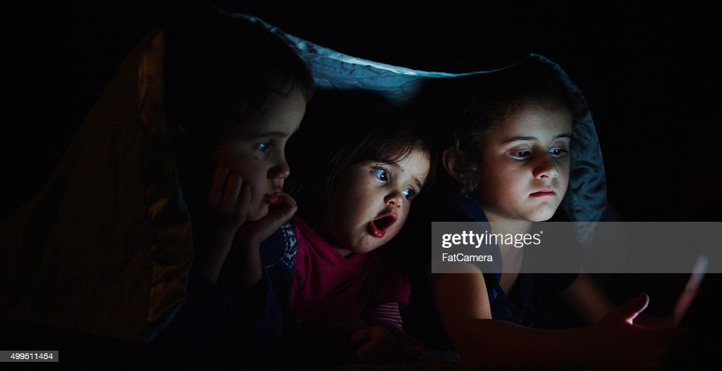 Siblings Watching a Movie Under a Blanket : Stock Photo