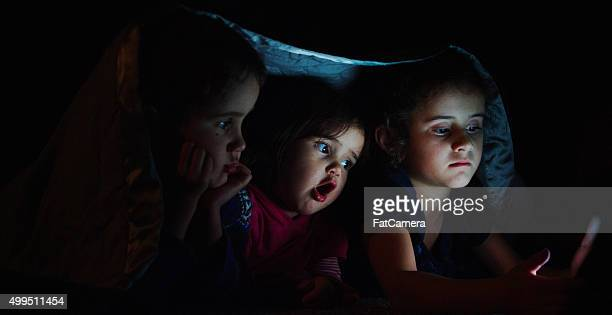 Siblings Watching a Movie Under a Blanket