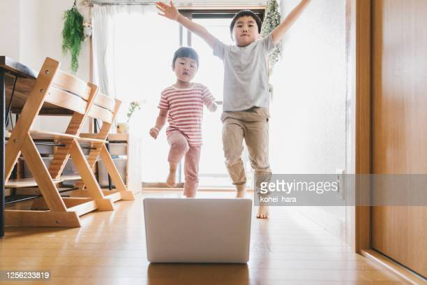 Siblings watching laptop and dancing at home
