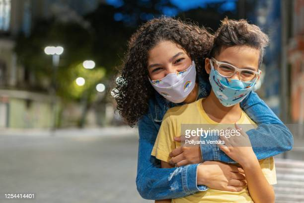 hermanos con mascarilla respiratoria n95 al aire libre por la noche - máscara protectora fotografías e imágenes de stock