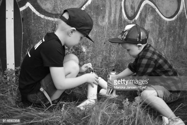 Siblings With Spray Paint Crouching On Grass