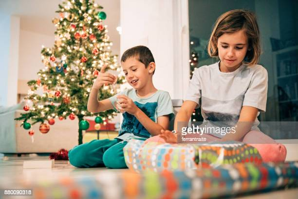 siblings wrapping presents together - mexican christmas stock photos and pictures