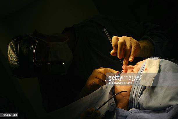 Sibongile Khumalo South African Doctor Rick peforms a nose plastic surgery on a British patient in Johannesburg on October 23 2008 Forget Africa's...
