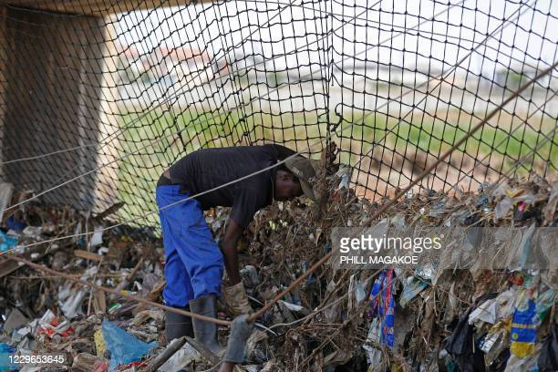 Sibusiso Dlomo a worker from Freshngo removes plastic deluge from litter trap nets and long line cables that was washed down under a bridge on the...