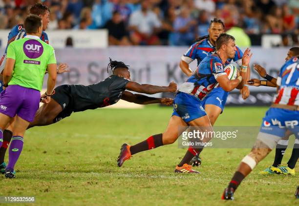 Sibusiso Nkosi of the Cell C Sharks tries to stop a driving Handre Pollard of the Vodacom Bulls during the Super Rugby match between Vodacom Blue...