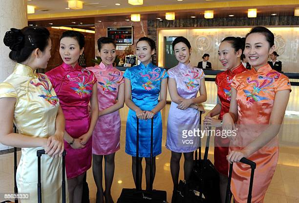 Sichuan Airlines flight attendants in cheongsam with Chinese phoenix embroidered on pose for a picture during a function at a hotel in Tianjing China...
