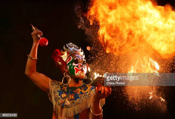 A Sichuan Opera actor performs fire breathing during a show of traditional operas at the Mei Lanfang Grand Theatre on February 26 2008 in Beijing...