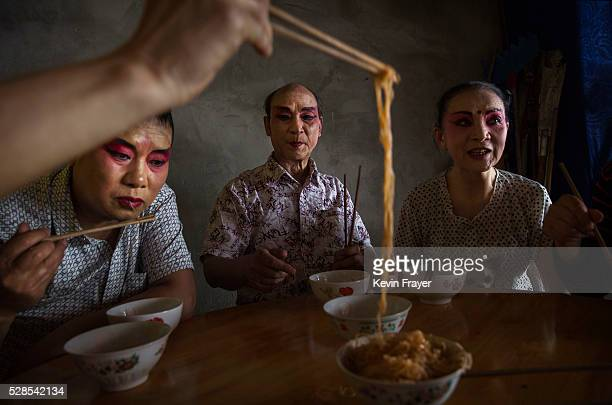 Sichuan Opera performers of the Jinyuan Opera Company eat lunch on May 3, 2016 during a break at the Dongyue Temple in Cangshan, Sichuan province,...