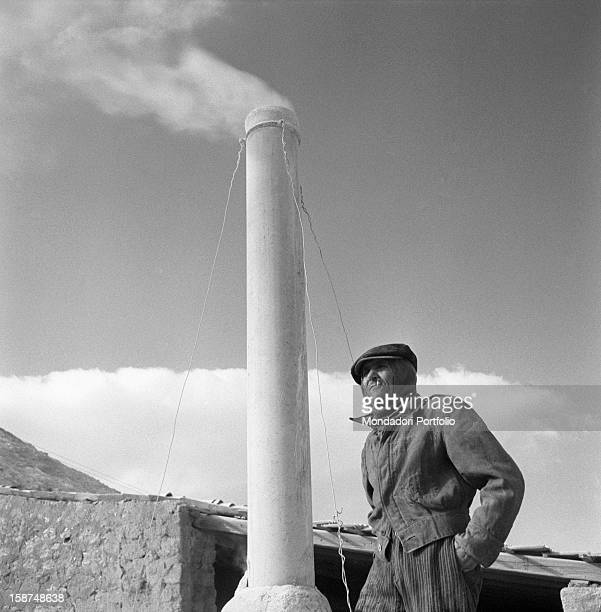 A Sicilian miner walking beside a chimney of the sulphur mine near Agrigento Sicily 1955