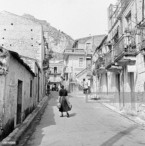 A Sicilian woman walking i a street of the city holding two amphoras Taormina 1955