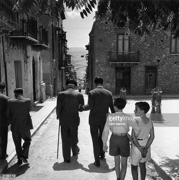 Sicilianborn gangster Charles 'Lucky' Luciano walking down a street in his native Sicily followed by local children mimicking his posture Whilst in...