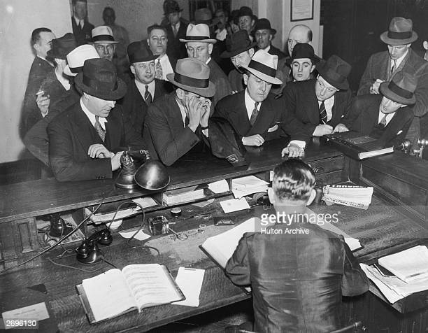 Sicilianborn mafia boss Charles 'Lucky' Luciano stands at a courtroom desk in New York City with his face in his hands as he is booked after his...
