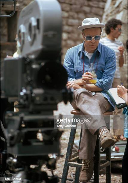 Sicily italy 1971 Franco Zeffirelli film director is sitting on a chair next to large filming camera holding a soda He has a sunglasses on and blue...