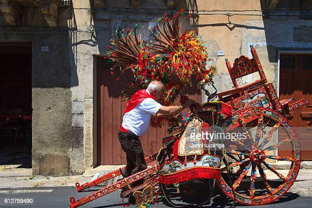 sicily, italy: man preparing painted cart for festival in vizzini - sicilia foto e immagini stock