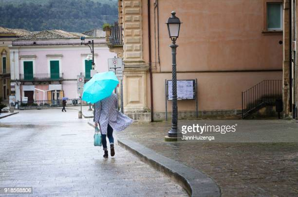 Sicily: Rainy-Windy Day in Baroque Town; Woman with Blue Umbrella
