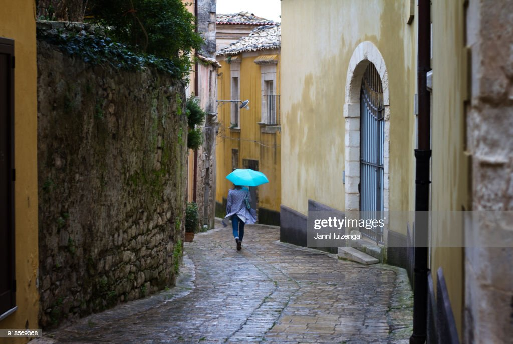Sicile: Journée pluvieuse et venteuse dans la ville Baroque; Femme avec parapluie bleu : Photo