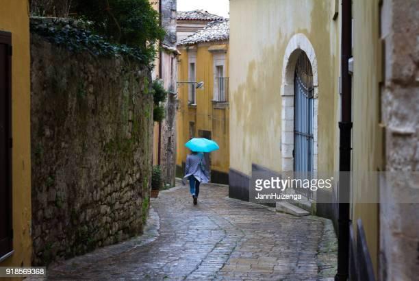 Sicile: Journée pluvieuse et venteuse dans la ville Baroque; Femme avec parapluie bleu