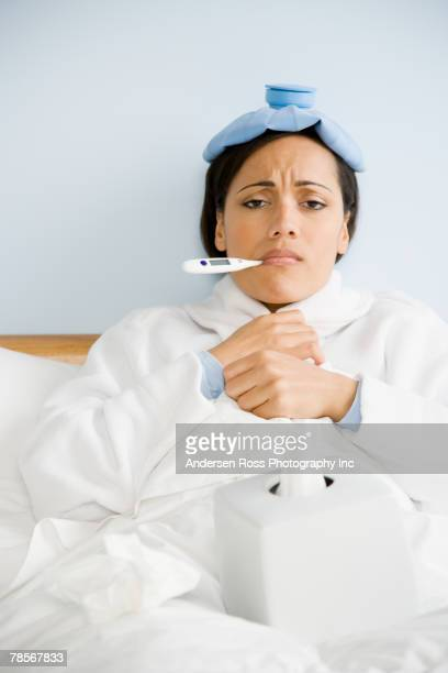 sick african american woman taking temperature - cold and flu stock photos and pictures