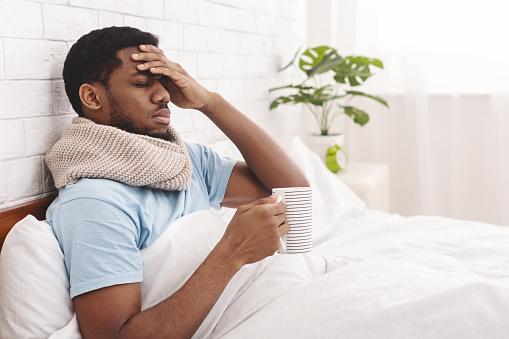 Sick african-american man drinking hot healing tea in bed 1149271136