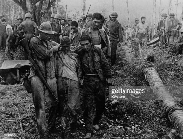 Sick and starving Japanese soldiers being taken down to the beach by American troops after the capture of an enemy stronghold on Guadalcanal in the...