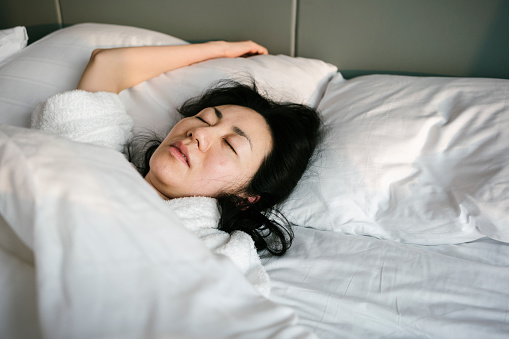 Sick and tired woman sleeping in the bed in early morning - gettyimageskorea