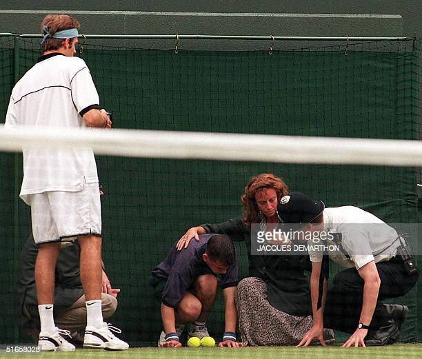 A sick ballboy is attended to by a line judge and a policeman whilst British player Greg Rusedski looks on 29 June at the Wimbledon Championships
