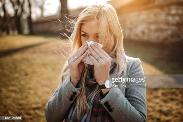 sick blonde blowing her nose - season stock pictures, royalty-free photos & images