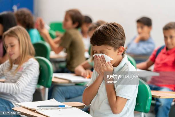 sick boy at the school blowing his nose in class - medical condition stock pictures, royalty-free photos & images