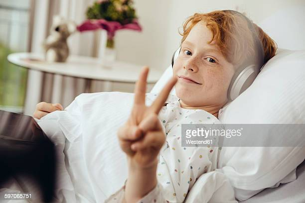 sick boy lying in hospital making victory sign, wearing head phones - krankheit stock-fotos und bilder