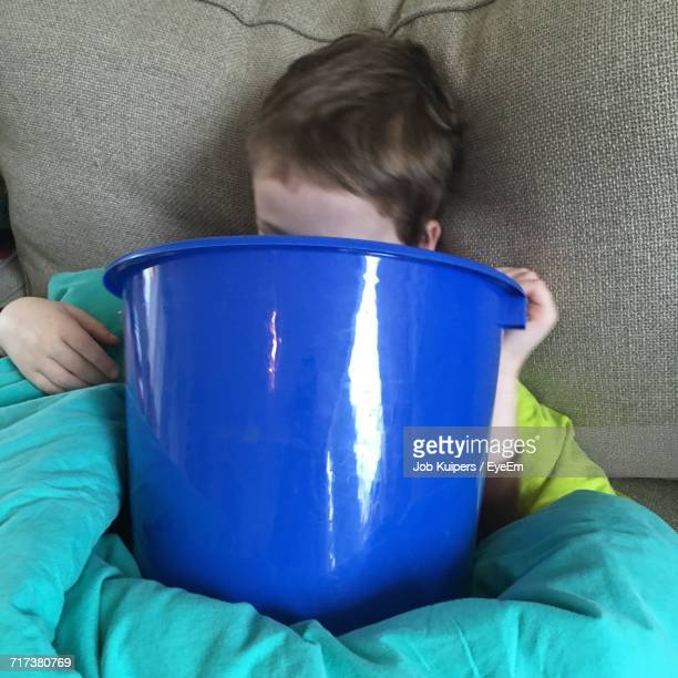 Sick Boy Vomiting In Bucket While Lying On Bed