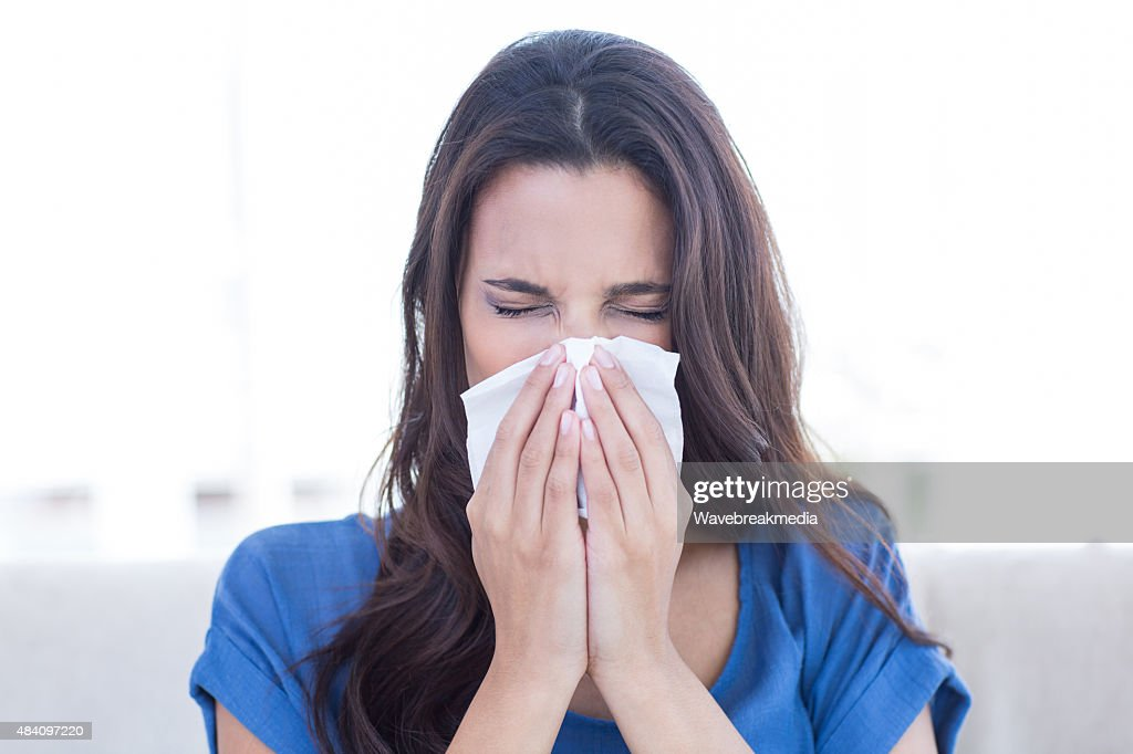 Sick brunette blowing her nose : Stock Photo