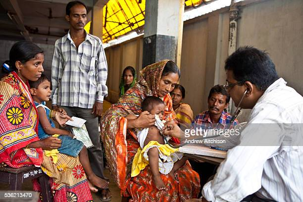 A sick child is examined by a doctor in the CINI health clinic while other families wait their turn Child In Need Institute is based in Kolkata India...