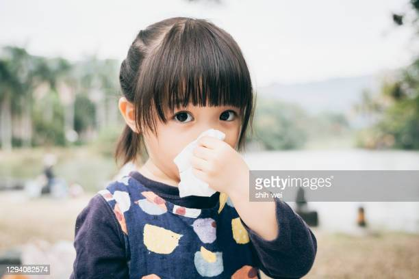 sick daughter wiping and cleaning nose - condition stock pictures, royalty-free photos & images