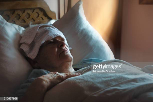 sick exhausted senior woman in bed with wet washcloth on her forehead - death stock pictures, royalty-free photos & images