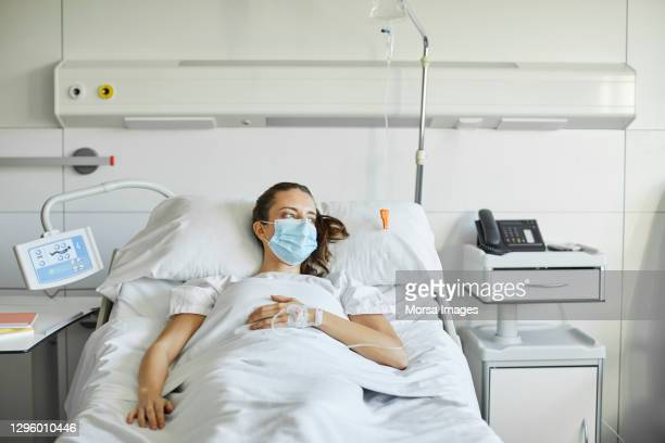 sick female lying on bed in icu during covid-19 - iv drip stock pictures, royalty-free photos & images