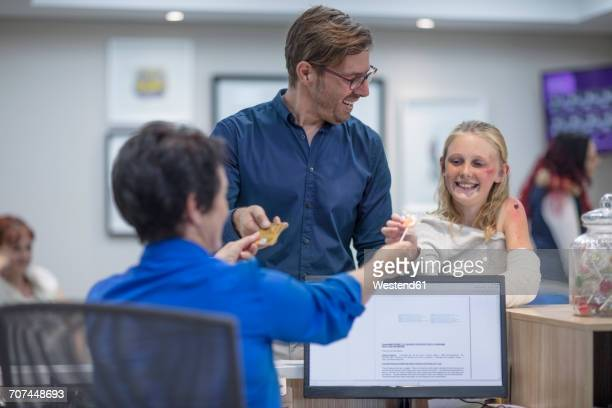 Sick girl getting lollipop from receptionist in hosptal