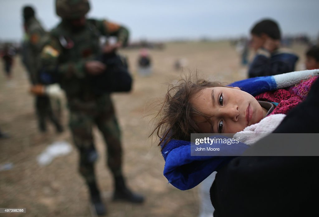 A sick girl is carried from her frontline village to a Kurdish-controlled area on November 16, 2015 to Sinjar, Iraq. Peshmerga forces carefully screened displaced Iraqis as they arrived, fearing enemy infiltrators and suicide bombers. Kurdish forces, with the aid of massive U.S.-led coalition airstrikes, liberated Sinjar from ISIL extremists, known in Arabic as Daesh, moving the frontline south. About one thousand villagers in Ghabosyeh fled north to Kurdish held territory, to take refuge camps or onward as refugees to Turkey or Europe.