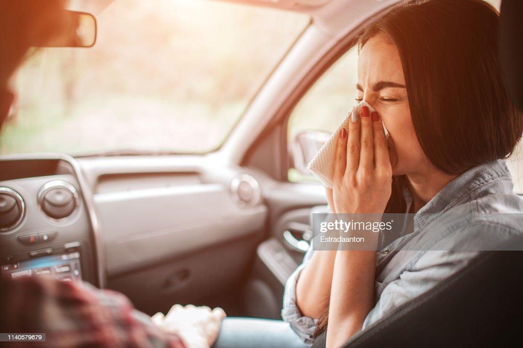 Ziek meisje is niezen in servet. Ze heeft haar ogen gesloten. Het is paiful voor haar om het te doen. Guy houdt zijn hand op haar been. : Stockfoto