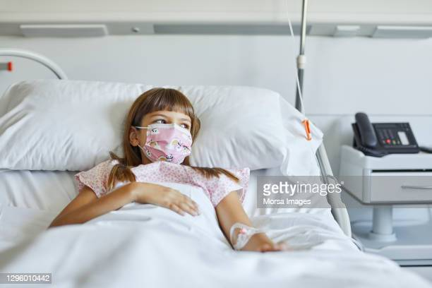 sick girl lying on bed in icu during covid-19 - illness stock pictures, royalty-free photos & images
