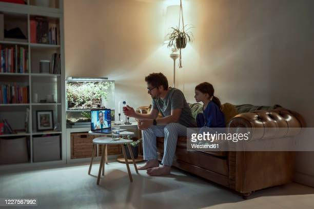 sick girl sitting by father discussing telemedicine with doctor over video call through laptop in living room at home - spain stock pictures, royalty-free photos & images